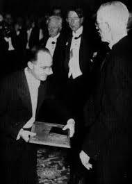 L'immagine è la fotografia della consegna del Premio Nobel a Fermi nel 1938